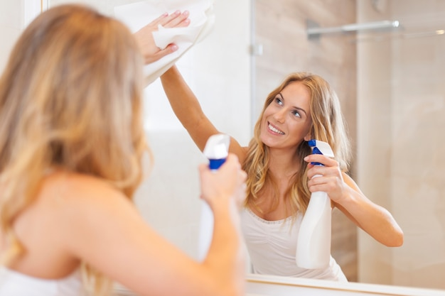Молодая блондинка чистит зеркало в ванной комнате