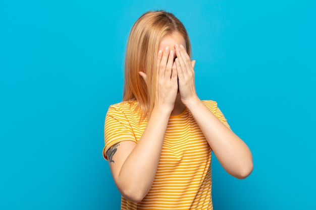 Young blonde woman covering eyes with hands with a sad, frustrated look of despair, crying, side view