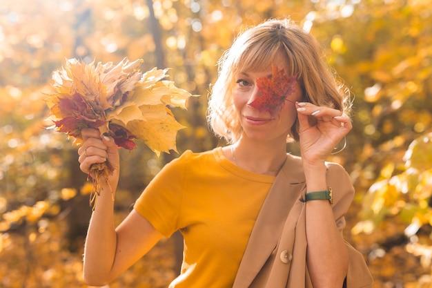 빨간 단풍잎으로 한쪽 눈을 덮고 있는 젊은 금발의 여자. 가을과 계절 개념입니다. 단풍과 야외 가을 여성 초상화 클로즈업
