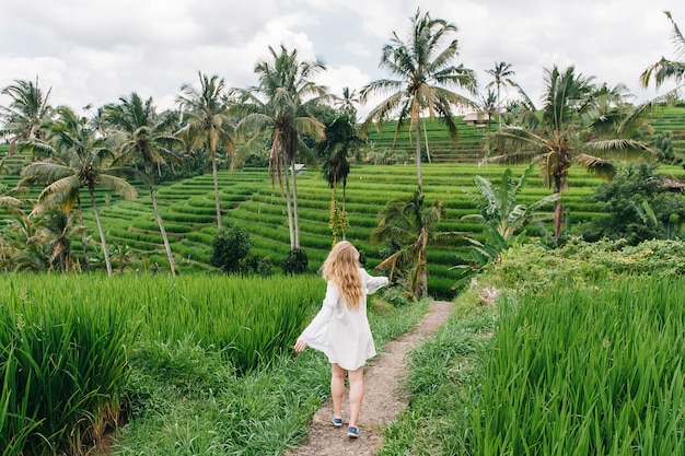 Young blonde woman dance on the rice fields of bali island, indonesia.