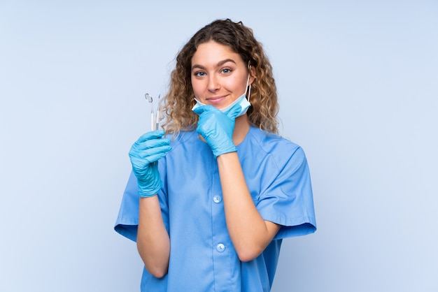 Young blonde woman dentist holding tools on blue wall laughing