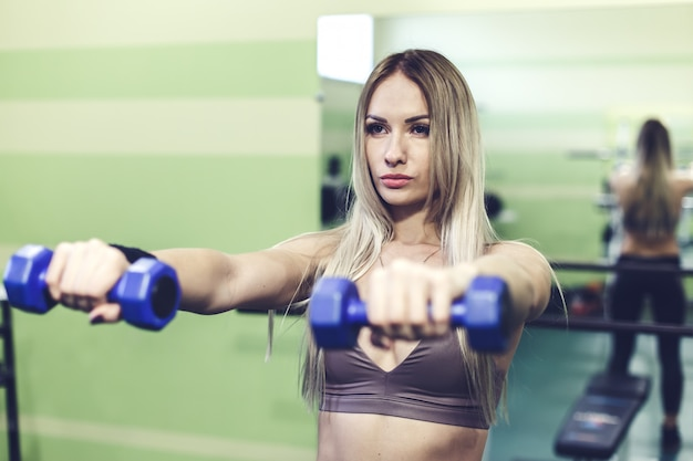 Young blonde woman doing exercises with dumbbells in a gym.