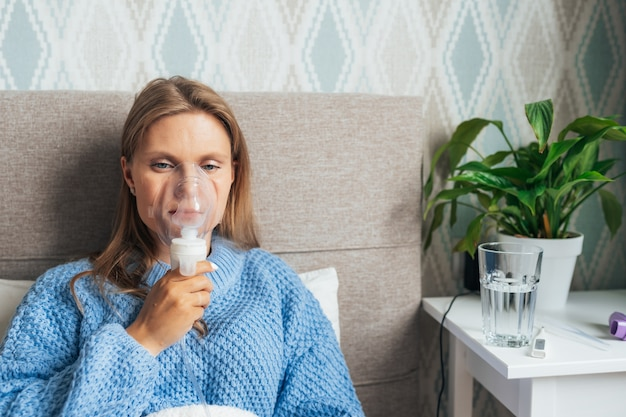 Young blonde woman doing inhalation with steam nebulizer at home.
