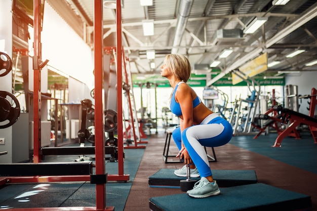 Young blonde woman doing squat