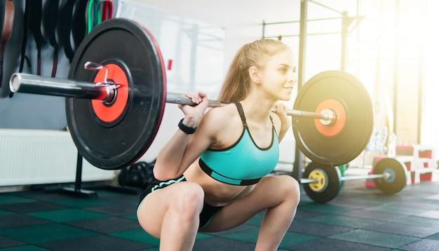 체육관에서 어깨에 바벨과 쪼그리고 앉는 젊은 금발의 여자