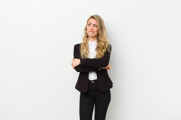 Young blonde woman doubting or thinking, biting lip and feeling insecure and nervous, looking to copy space on the side on white wall