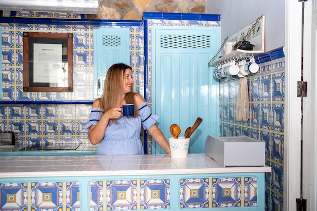 Young blonde woman dressed in a blue dress drinking a cup of coffee in a vintage blue ceramic kitchen.