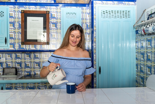 Young blonde woman dressed in a blue dress serving a cup of tea in a vintage blue ceramic kitchen.