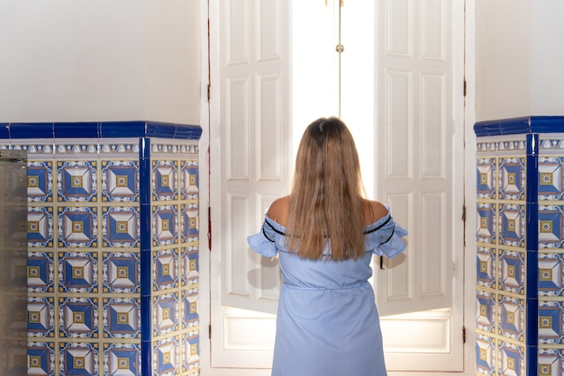 그녀의 집의 창문을 여는 파란 드레스를 입은 젊은 금발의 여자.