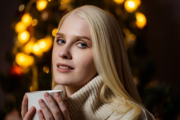 A young blonde woman drinks fragrant cocoa at home near a christmas tree.