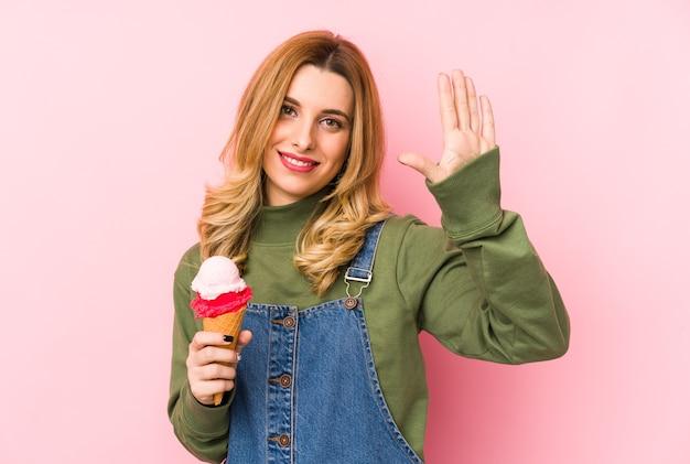 Молодая белокурая женщина ест мороженое изолировала усмехаясь веселый показ номер пять с пальцами.
