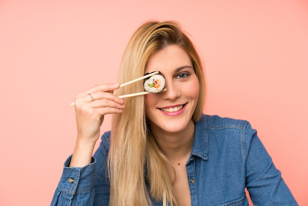 Young blonde woman eating sushi over pink wall
