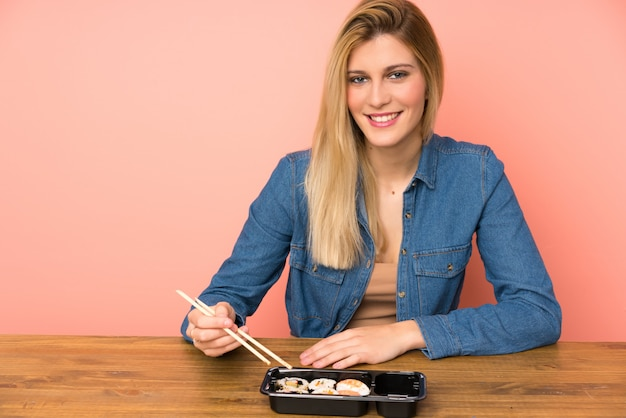 Young blonde woman eating sushi
