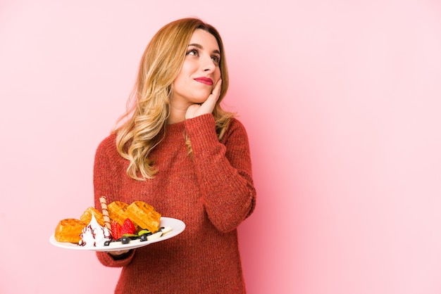 Young blonde woman eating a waffle dessert isolated looking sideways with doubtful and skeptical expression.