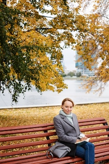 Young blonde woman in elegant clothes sitting under fall foliage in city park