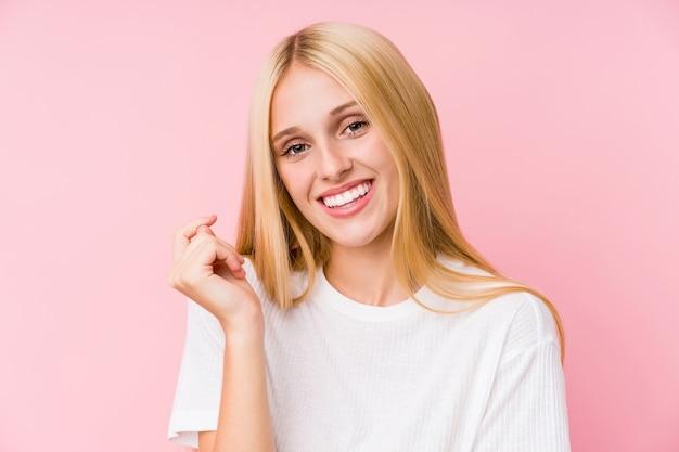 Молодая блондинка лицо крупным планом, изолированные на розовой стене