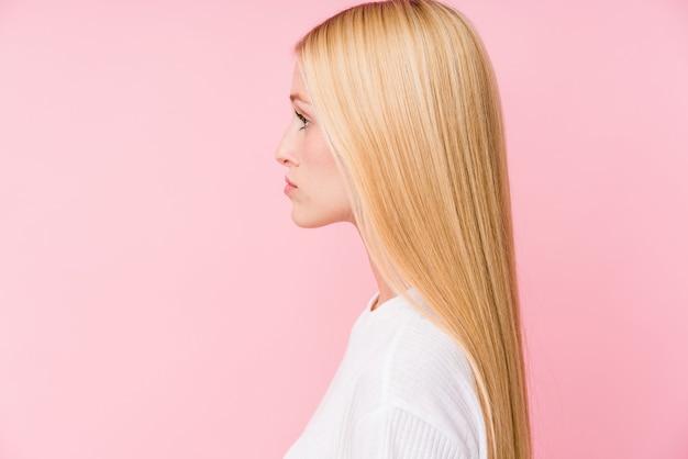분홍색 벽에 고립 된 젊은 금발의 여자 얼굴 근접 촬영