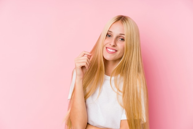 Young blonde woman face closeup isolated on a pink wall