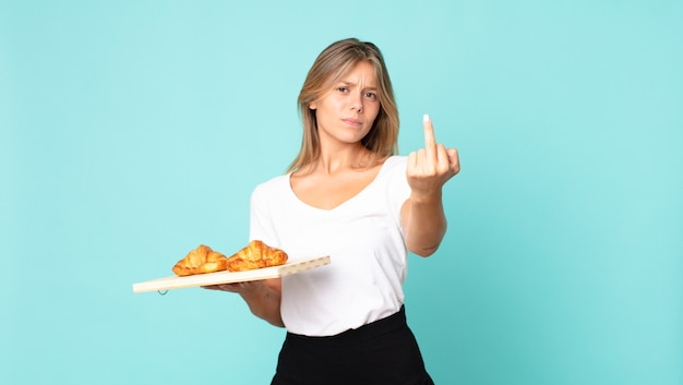 Young blonde woman feeling angry, annoyed, rebellious and aggressive and holding a croissant tray