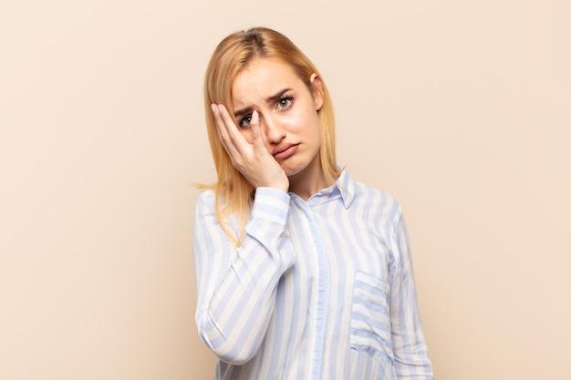 退屈で退屈で退屈な仕事の後、退屈で欲求不満で眠そうな若い金髪の女性が、手で顔を持っている
