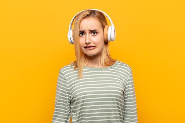 Молодая блондинка чувствует себя невежественной, растерянной и неуверенной в том, какой вариант выбрать, пытаясь решить проблему