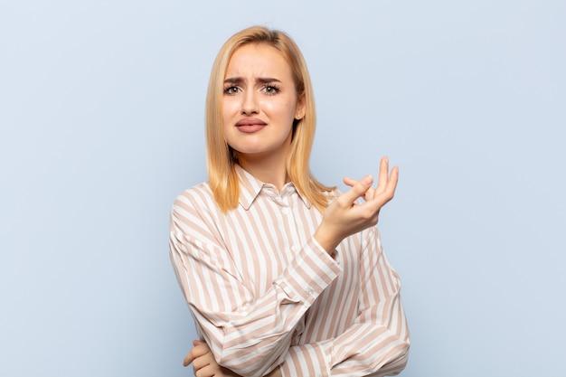 Молодая блондинка чувствует себя смущенной и невежественной, гадая над сомнительным объяснением или мыслью