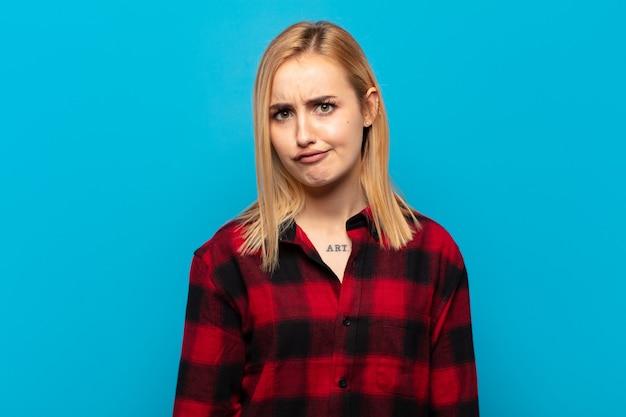 Молодая блондинка чувствует себя смущенной и сомнительной, задается вопросом или пытается выбрать или принять решение