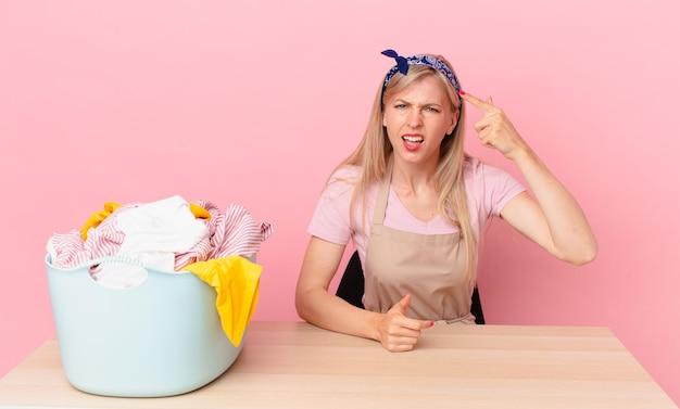 Молодая блондинка смущена и озадачена, показывая, что вы сошли с ума. концепция стирки одежды