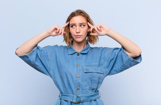 若いブロンドの女性が混乱したり疑問を感じたり、アイデアに集中したり、一生懸命考えたり、フラットカラーの壁の側にスペースをコピーしたりすることを探している