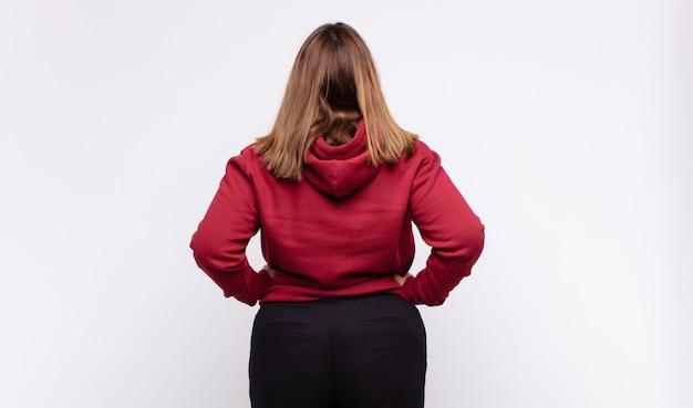 혼란 스럽거나 전체 또는 의심과 질문을 느끼는 젊은 금발의 여자, 궁금해, 엉덩이에 손, 후면보기