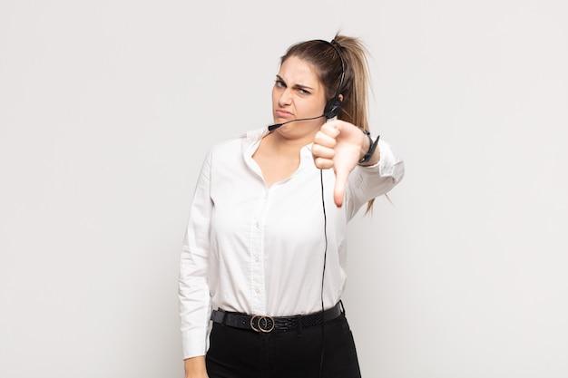 심각한 표정으로 엄지 손가락을 보여주는 십자가, 화가, 짜증, 실망 또는 불쾌감을 느끼는 젊은 금발의 여자