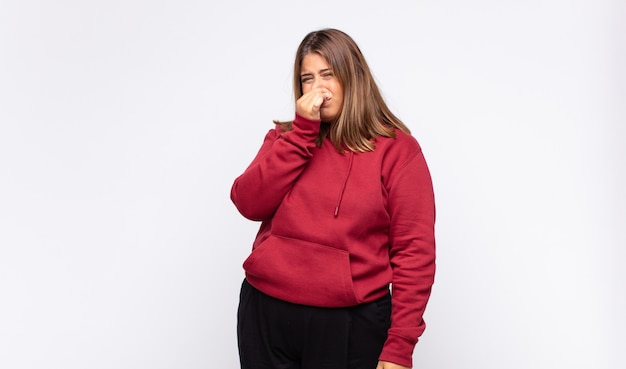 Young blonde woman feeling disgusted, holding nose to avoid smelling a foul and unpleasant stench