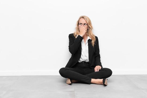 床に座っている悪臭と不快な悪臭のにおいを避けるために鼻を抱えて嫌悪感を感じる若いブロンドの女性