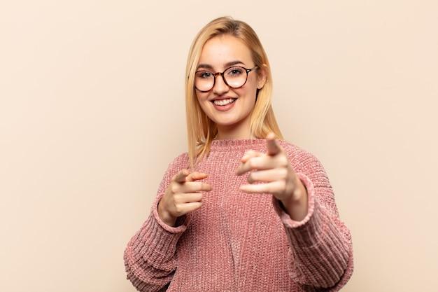 Молодая блондинка чувствует себя счастливой и уверенной обеими руками и смеется, выбирая вас