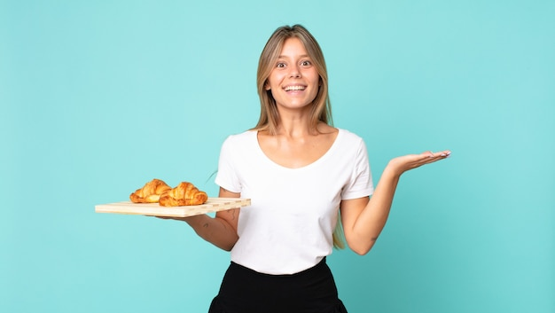 Young blonde woman feeling happy and astonished at something unbelievable and holding a croissant tray