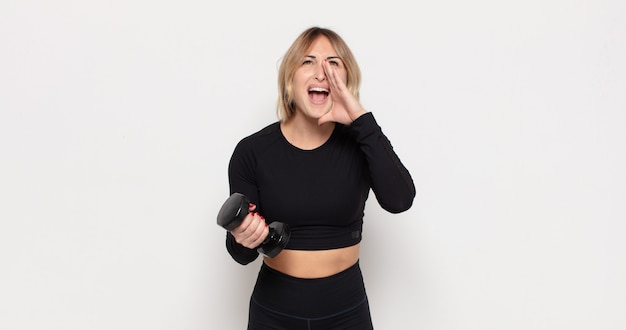 Young blonde woman feeling happy, excited and positive, giving a big shout out with hands next to mouth, calling out