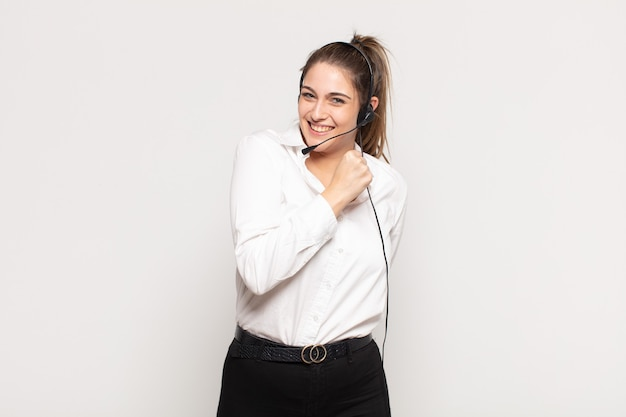 도전에 직면하거나 좋은 결과를 축하 할 때 행복하고, 긍정적이고, 성공하고, 동기 부여 된 젊은 금발의 여자