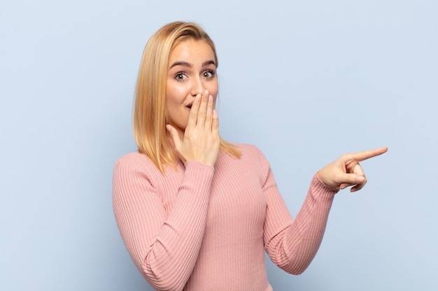 Young blonde woman feeling happy, shocked and surprised, covering mouth with hand and pointing to lateral copy space