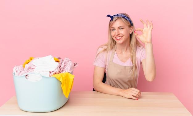 Молодая белокурая женщина чувствует себя счастливой, показывая одобрение с нормальным жестом. концепция стирки одежды