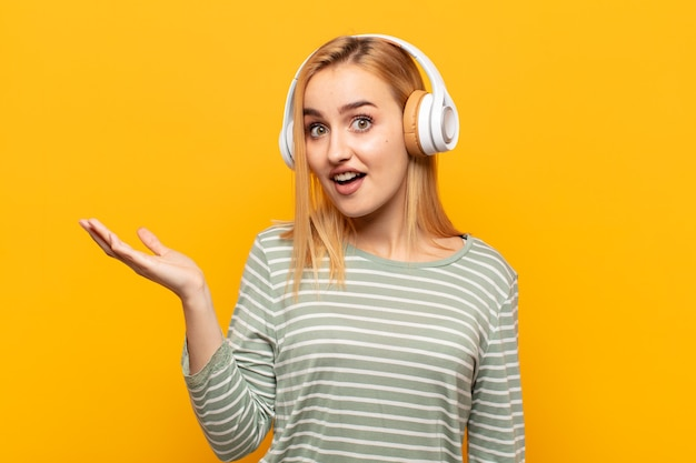Молодая блондинка чувствует себя счастливой, удивленной и веселой, улыбается с позитивным настроем, реализует решение или идею