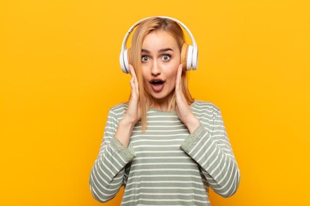 若い金髪の女性が恐怖とショックを感じ、手を頭に上げ、間違いでパニックに陥る