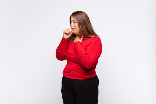 Молодая блондинка чувствует себя плохо с симптомами гриппа и болью в горле, кашляет с прикрытым ртом