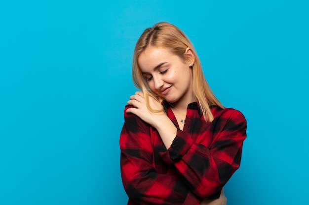Young blonde woman feeling in love, smiling, cuddling and hugging self