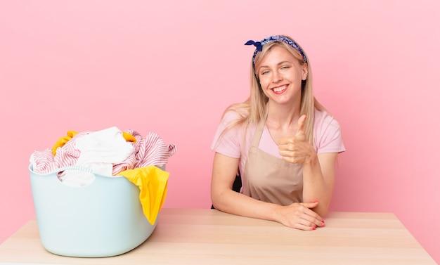 Молодая блондинка чувствует себя гордой, позитивно улыбается с большими пальцами руки вверх. концепция стирки одежды