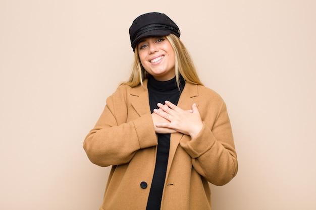 Молодая блондинка, чувствуя себя романтично, счастливо и влюбленно, весело улыбаясь и держась за руки близко к сердцу у плоской стены