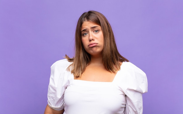 若い金髪の女性が悲しげで悲しげな表情で泣き叫び、否定的で欲求不満な態度で泣いている