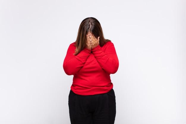 若いブロンドの女性は、悲しみ、欲求不満、神経質、落ち込んでいる、両手で顔を覆って、泣いている