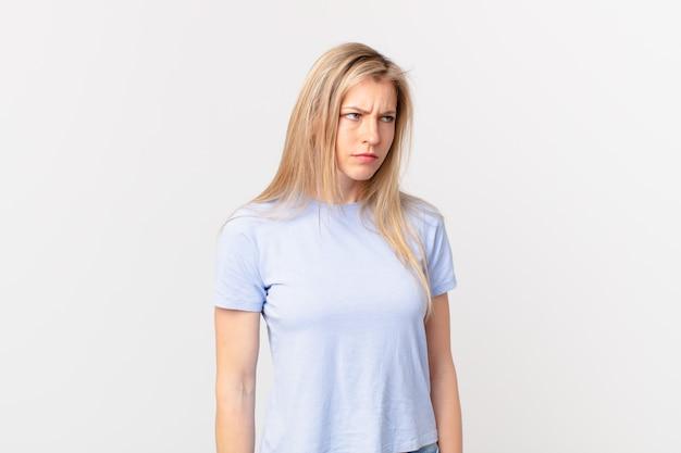 Молодая блондинка грустит, расстроена или злится и смотрит в сторону