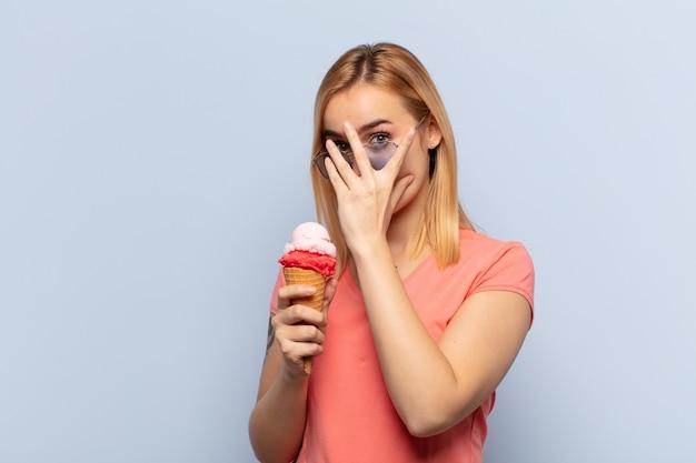 Молодая блондинка чувствует себя напуганной или смущенной, подглядывает или шпионит с полуприкрытыми руками глазами