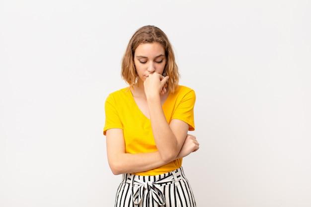 Молодая блондинка, чувствуя себя серьезной, вдумчивой и обеспокоенной, глядя вбок, прижимая руку к подбородку над цветной стеной